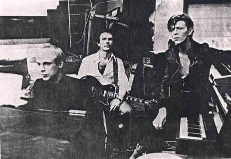 Brian Eno, Robert Fripp e David Bowie juntos no estúdio em Berlim, 1977.